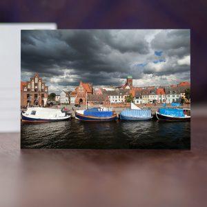 Wismars Alter Hafen mit Lohberg, Wassertor, Kirche St. Nikolai und davor: Fischverkaufsboote von hinten.